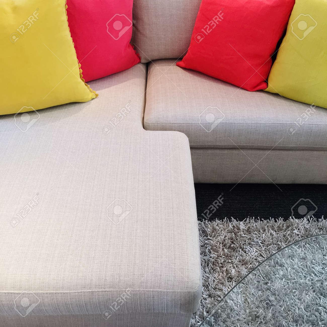 Bright red and yellow cushions decorating gray corner sofa.