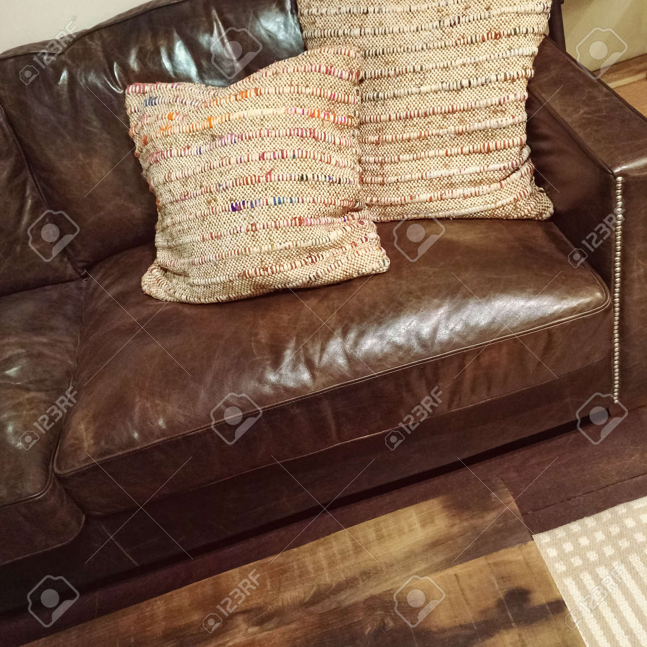 - Classic Brown Leather Sofa With Two Decorative Cushions. Stock