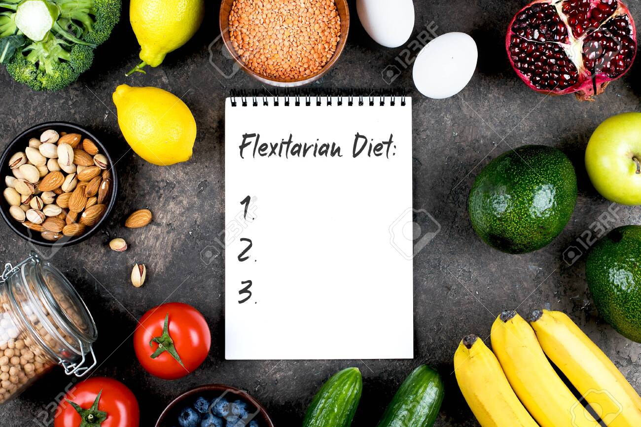Flexitarian Diet Concept. Green vegetables, tomatoes, nuts, fruits, lentils, chickpeas, greens and empty notebook blank on grey concrete table. Flat lay, top view, copy space - 143698383