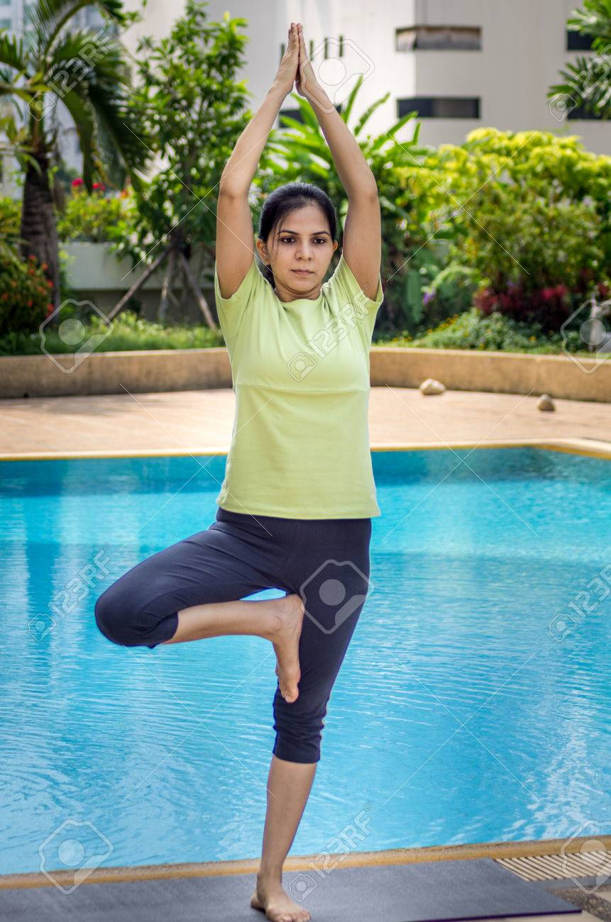A woman practicing a yoga pose standing on one leg and arms lifted..