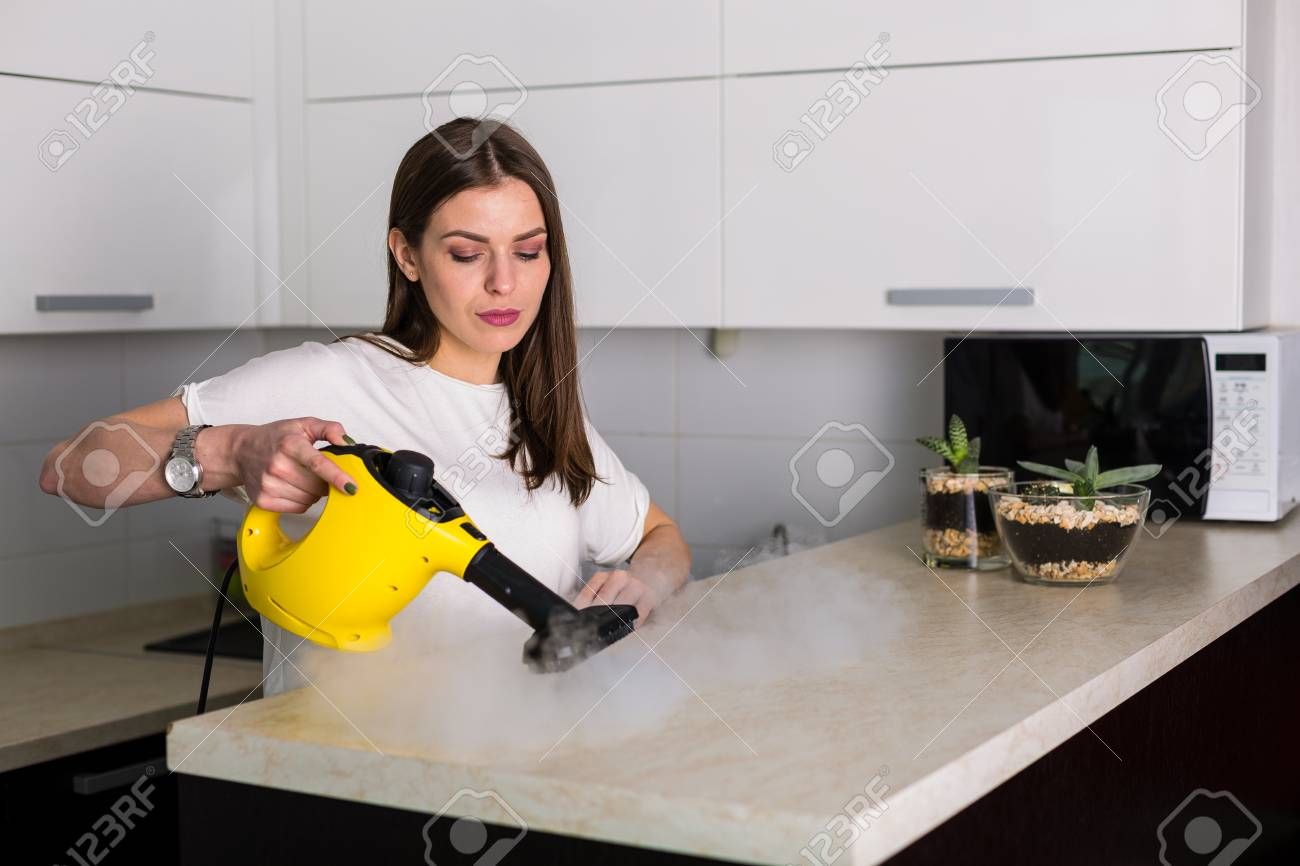 Young Beautiful Woman Cleaning Kitchen With Steam Cleaner Stock ...