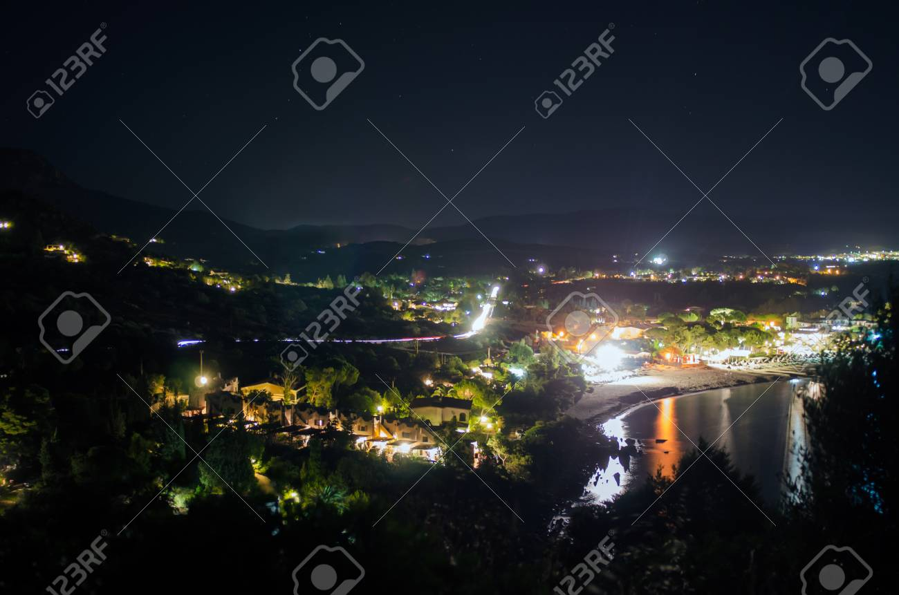 Coastal Landscape In The Night With Lights, Colors, Hills And Beach.  Villasimius Campus