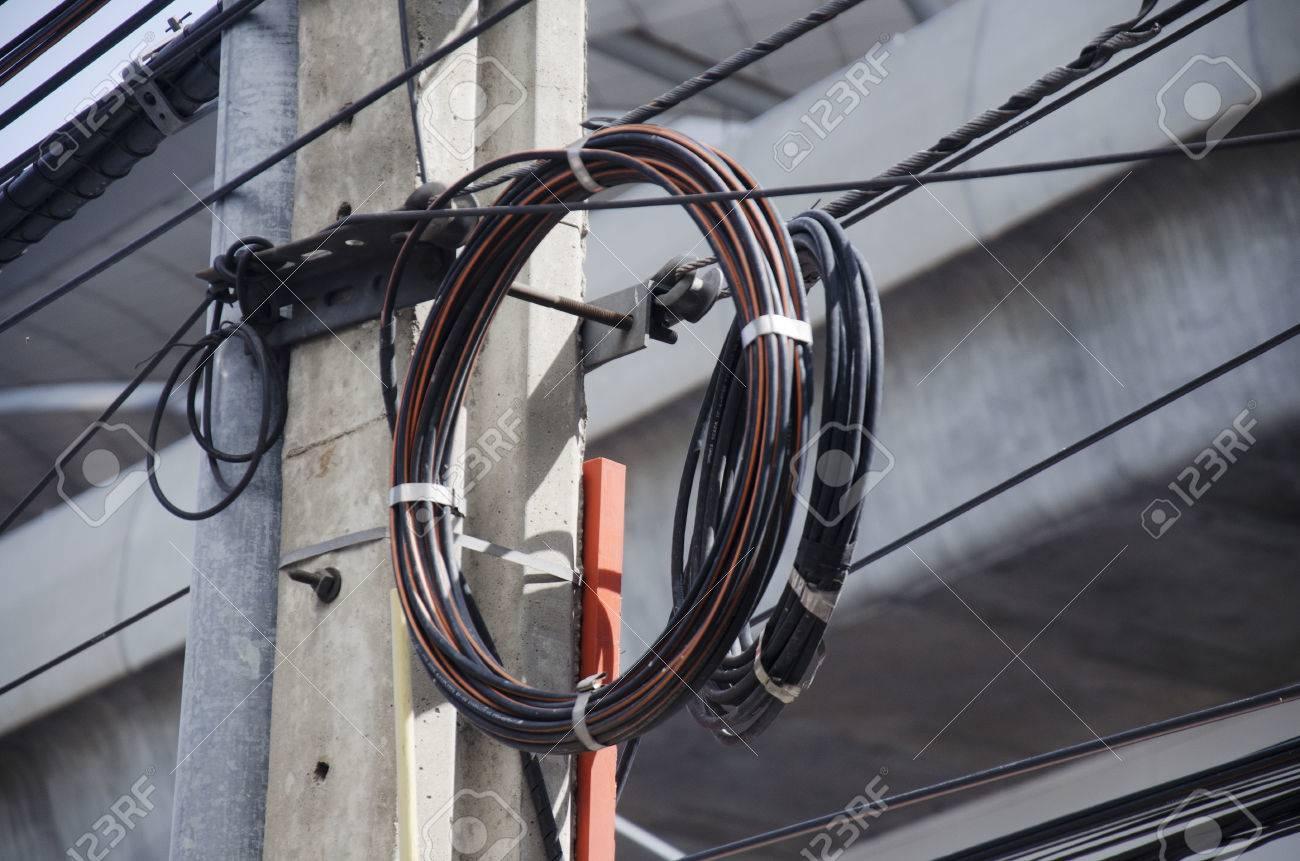 many wires messy with power line cables, transformers and phone lines on old  electricity pillar