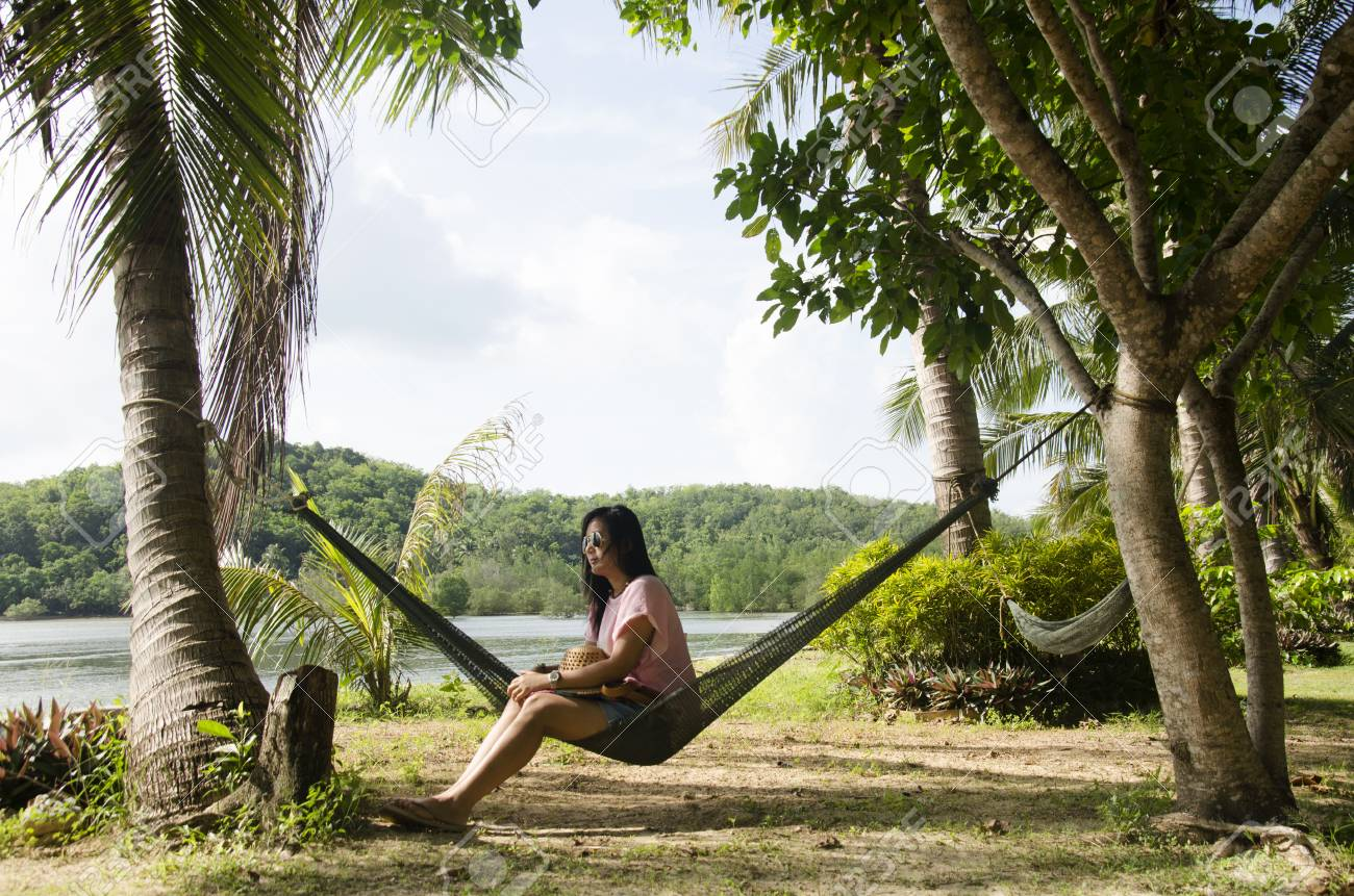 Asian Women Sit And Relaxing On Furniture Hammock Hanging Between ...