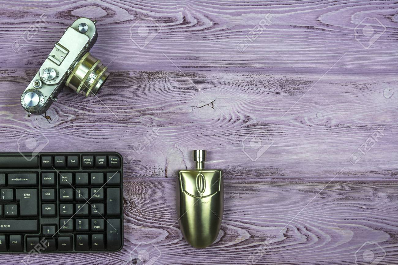 Keyboard, retro film camera, flask for cognac in the form of