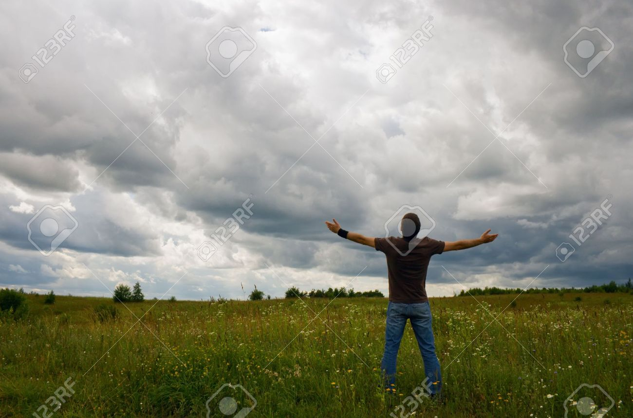 man standing on the field and raising his hands up to the clouds Stock Photo - 5258589