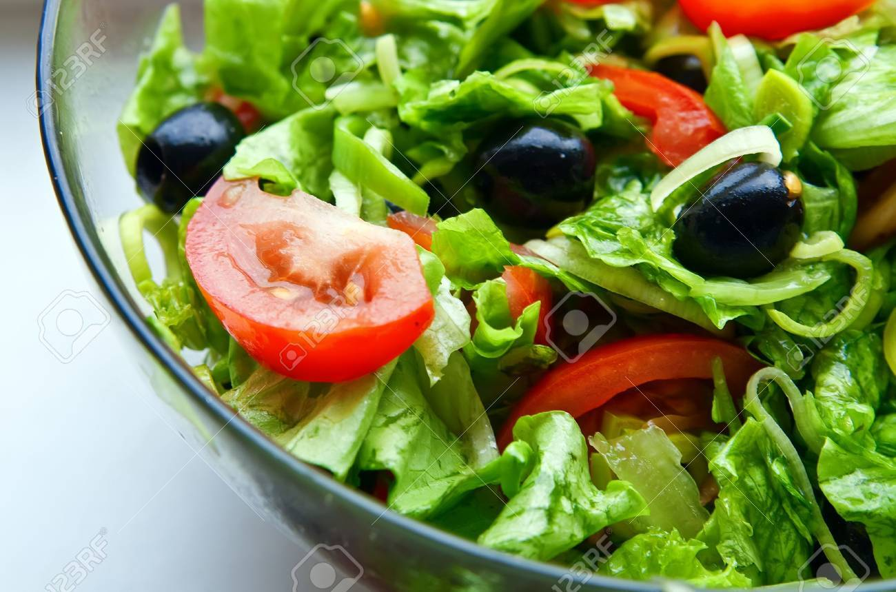 Close Up Healthy Vegetable Salad With Tomatoes Lettuce Onion And Black Olives Stock