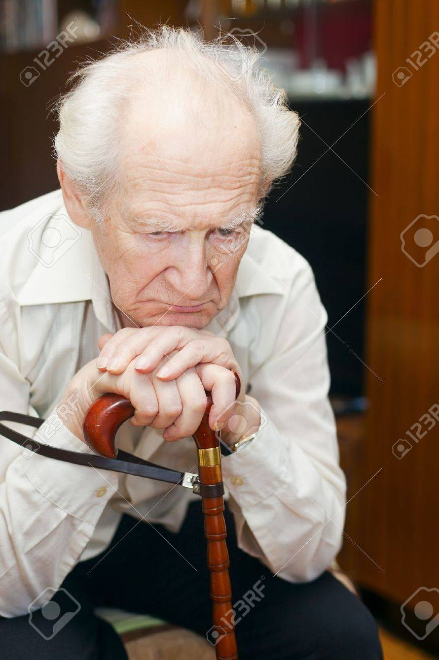 unhappy old man holding his cane Stock Photo - 12537796