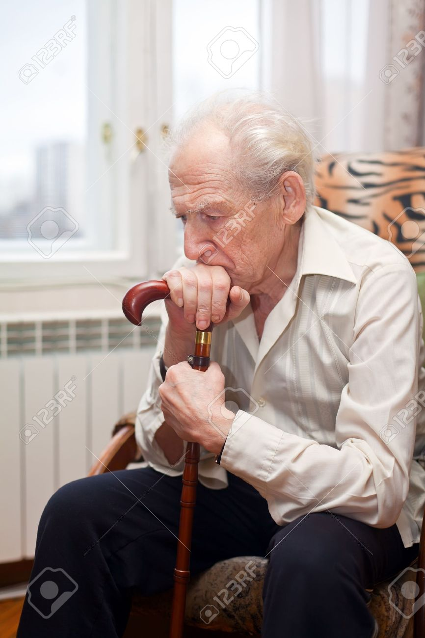 sad lonely old man sitting in an armchair with his cane - 13200219