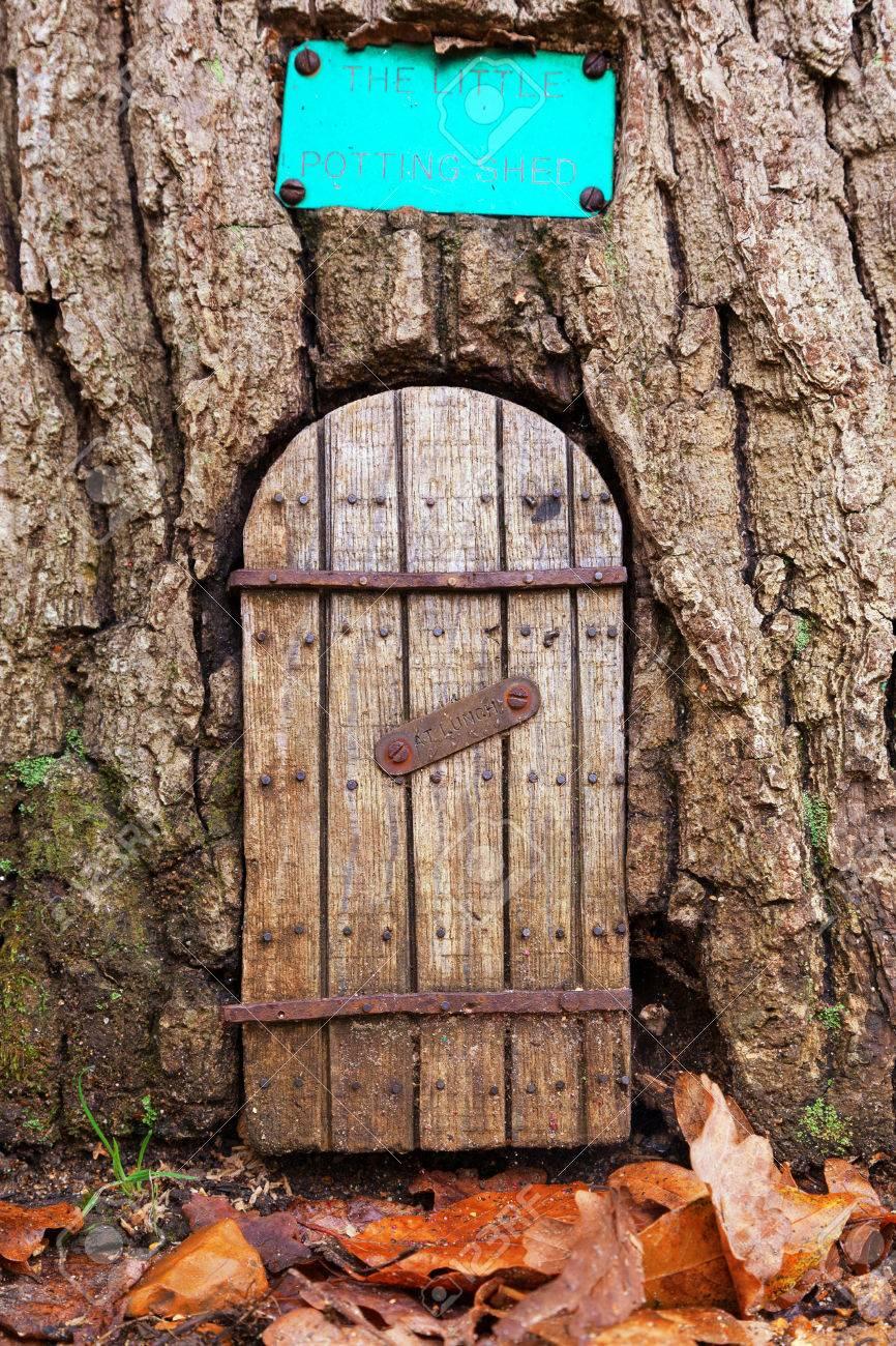 Porte De Fée Dans Un Tronc D'arbre Avec Des Feuilles D'automne Sur Le Sol  En Face De L'entrée. Avec Un Espace Pour Le Texte. Le Petit Abri De  Rempotage Est Fermé, Au