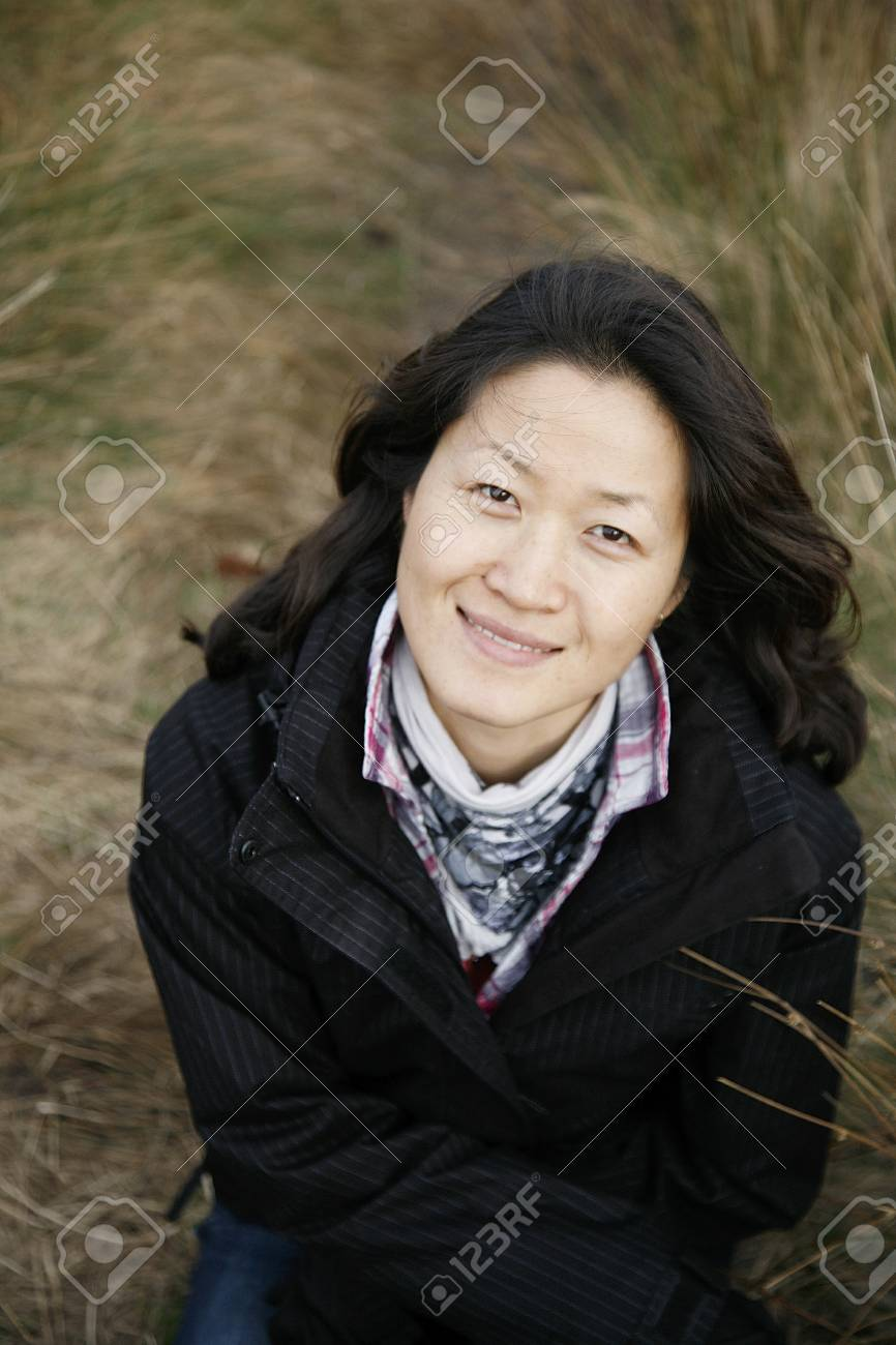 Portrait smiling asian woman looking up camera in the field Stock Photo - 12793349