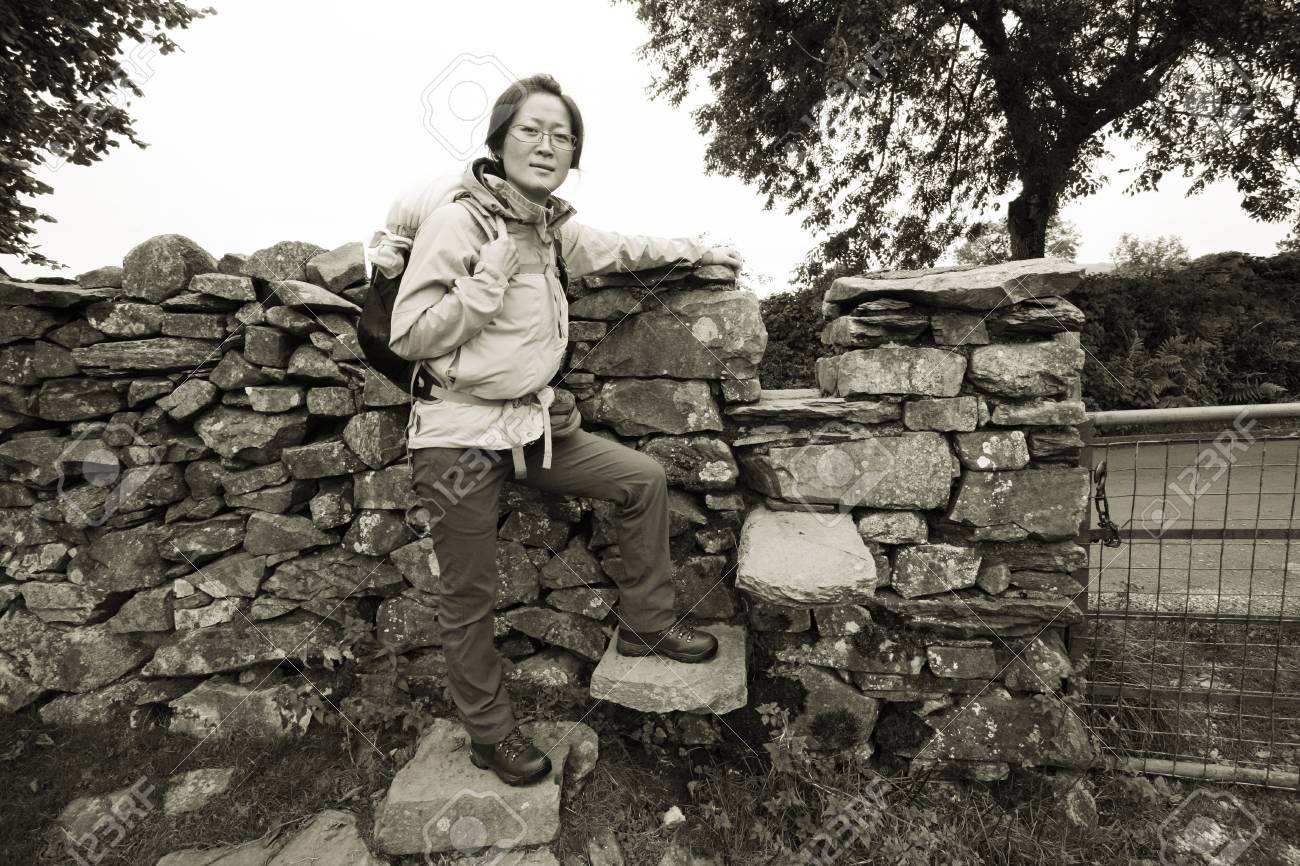 An East Asian Woman, climb the stone wall, hiking in Lake District, Cumbria, UK. Stock Photo - 24054106