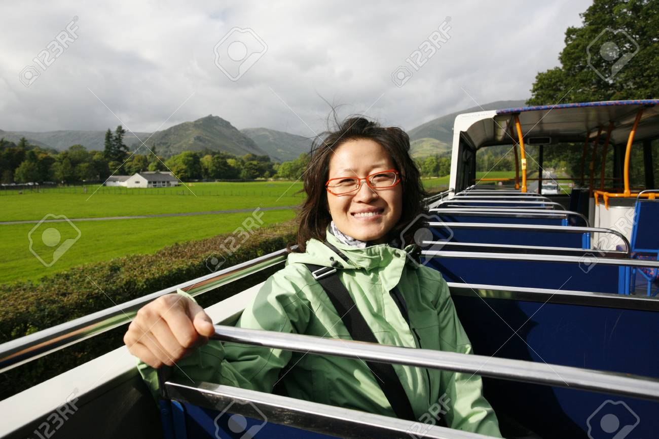 Smiling East Asian Woman on a tour bus, Lake District, Cumbria, UK. Stock Photo - 24054153