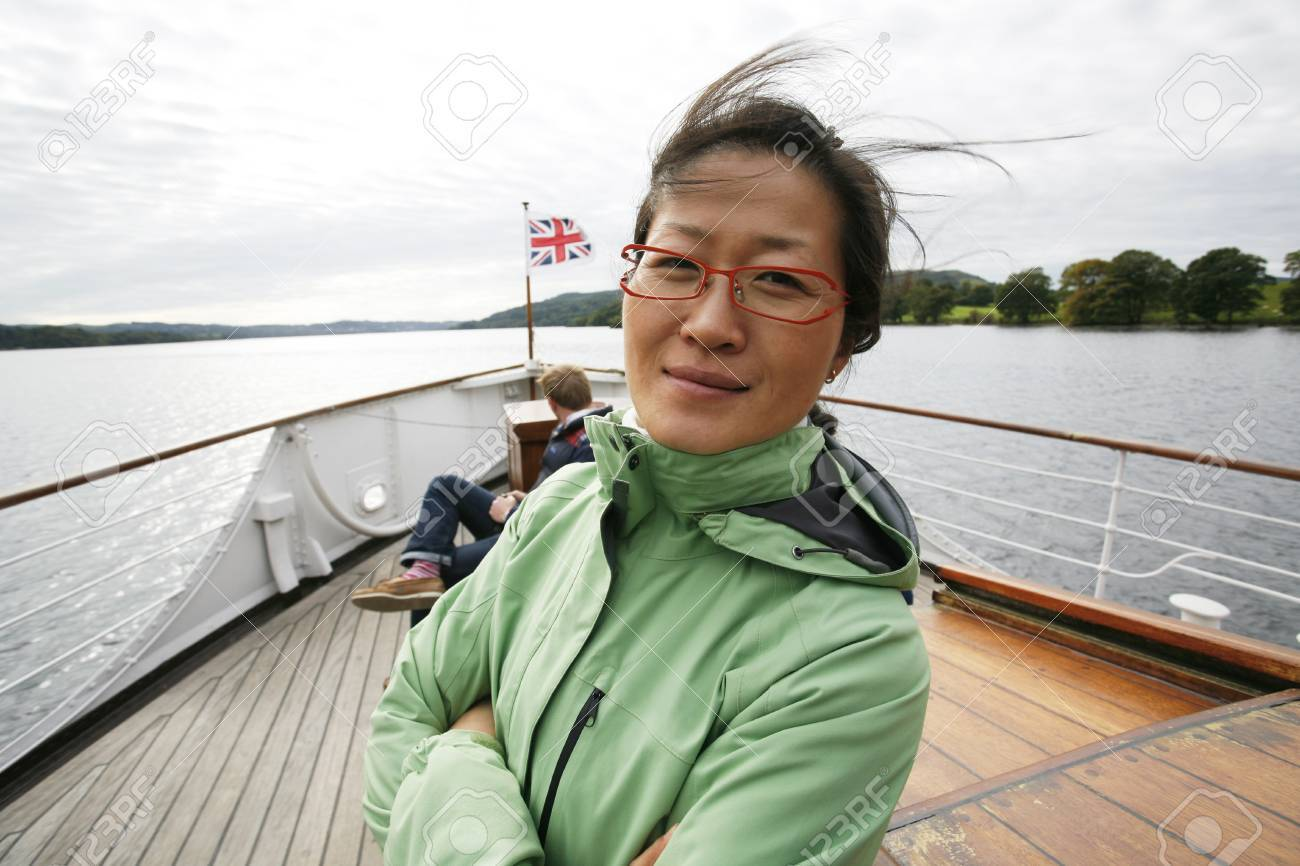 An East Asian Woman, hair blown by wind, looking at camera, on a tour boat, Windermere, Lake District, Cumbria, UK. Stock Photo - 24054160