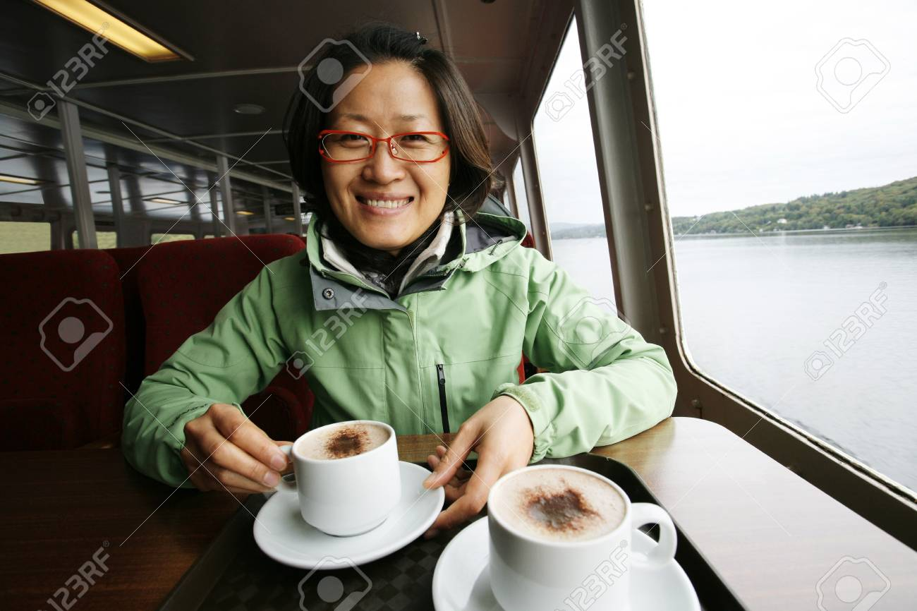 Smiling East Asian Woman on a tour boat, Windermere, Lake District, Cumbria, UK. Stock Photo - 24048147