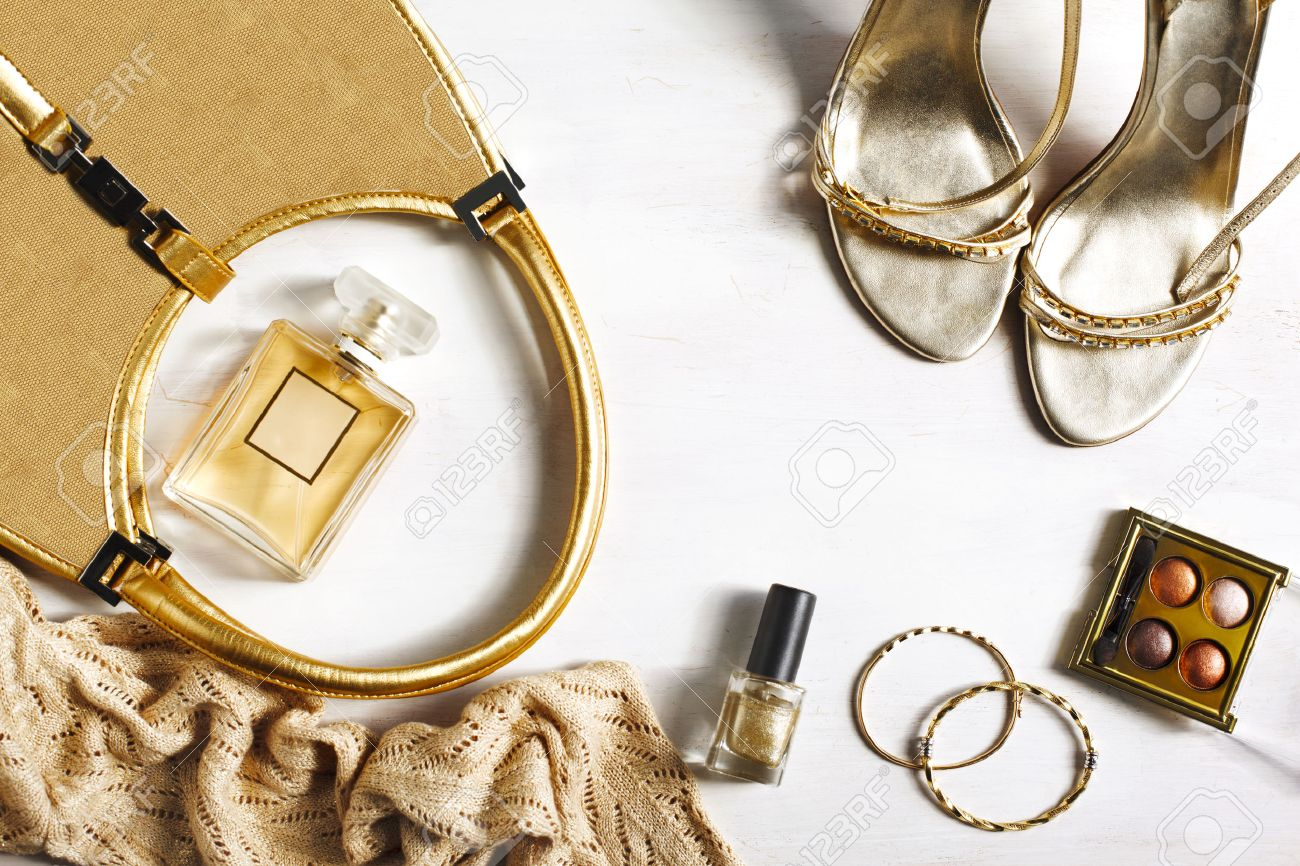 Women's set of fashion accessories in golden color on wooden background: shoes, handbag, perfume and cosmetics - 55136602