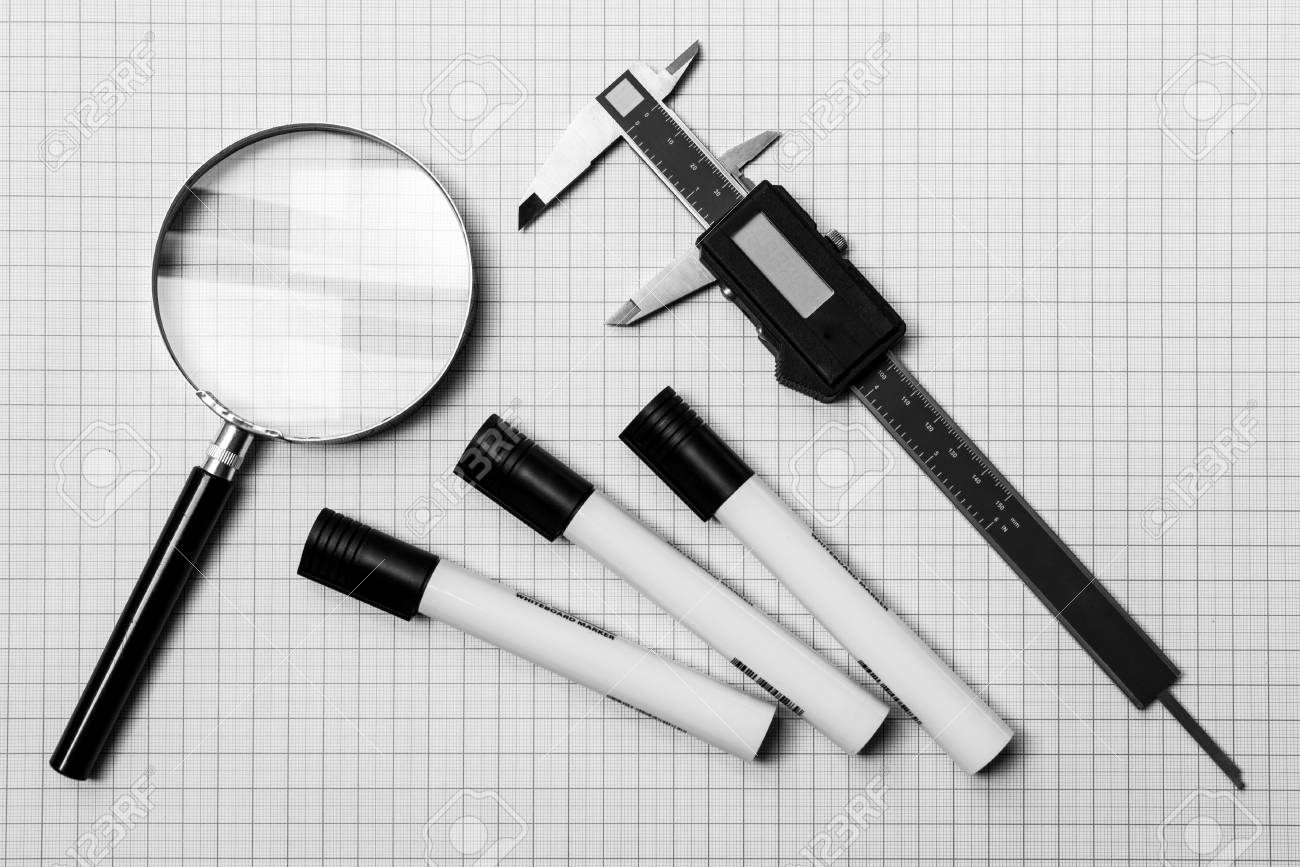 magnifying glass electronic slide calliper and pens on a graph paper stock photo 46725584
