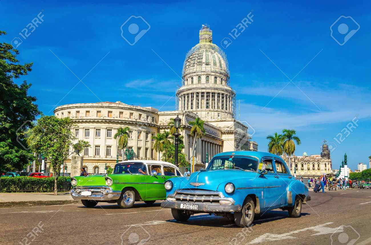 HAVANA, CUBA - DECEMBER 2, 2013: Old classic American cars rides in front of the Capitol. Before a new law issued on October 2011, cubans could only trade cars that were on the road before 1959. Stock Photo - 40537391