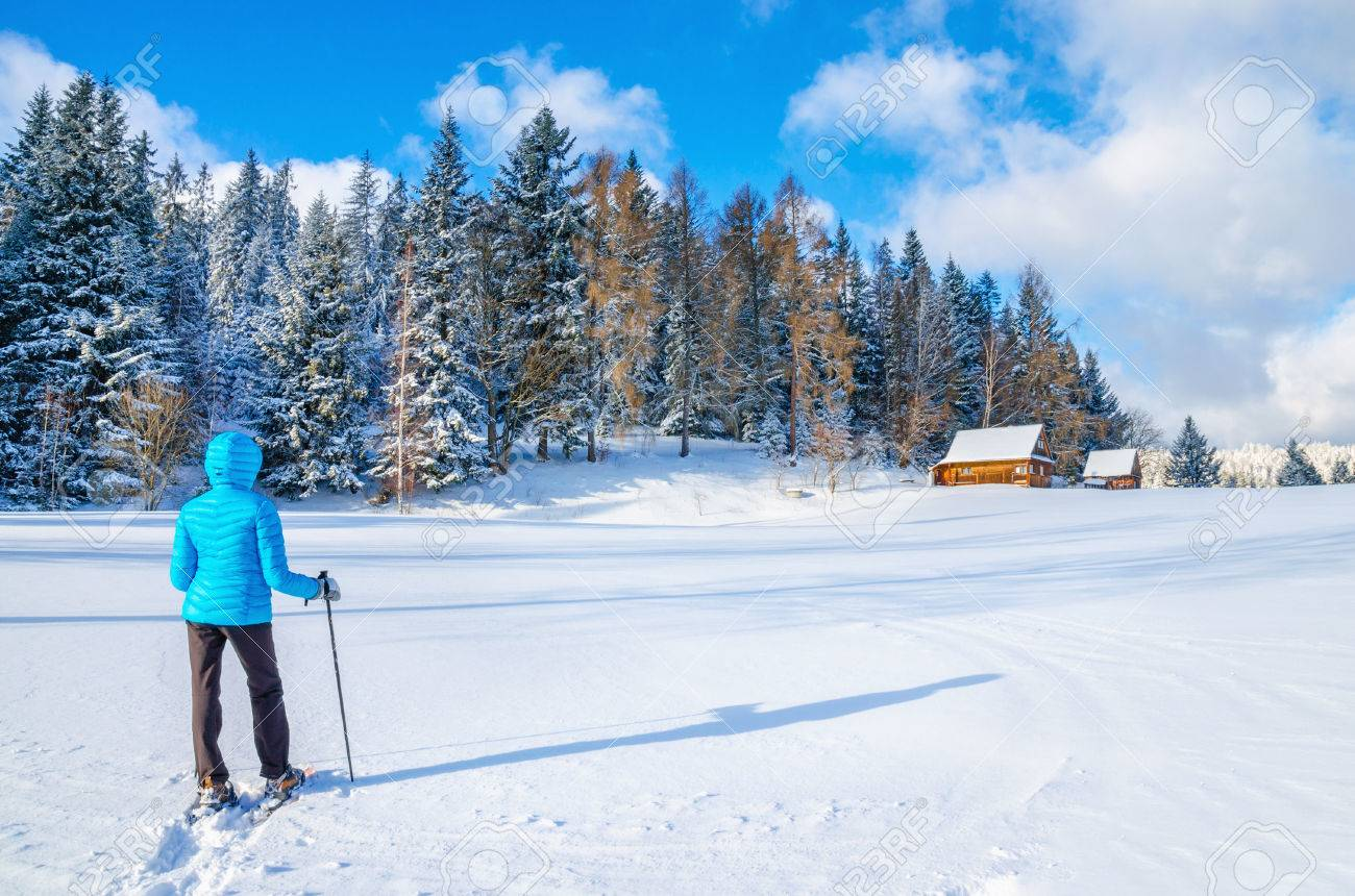 Young woman in blue down jacket walking towards remote mountain hut during cold winter Stock Photo - 40182080