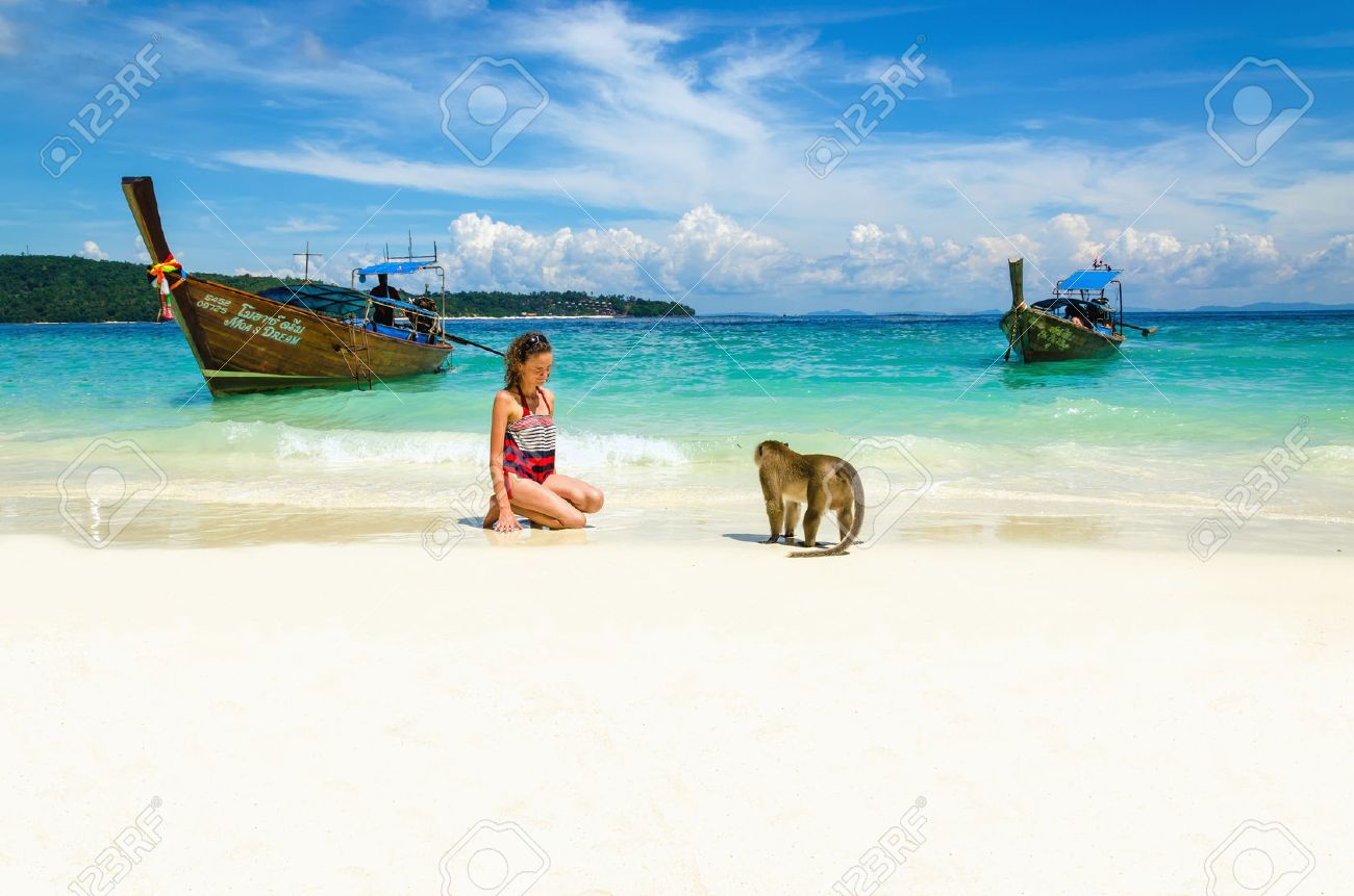 Longtail boat and monkeys waiting for food in Monkey Beach, Phi Phi Islands, Thailand Stock Photo - 40053614