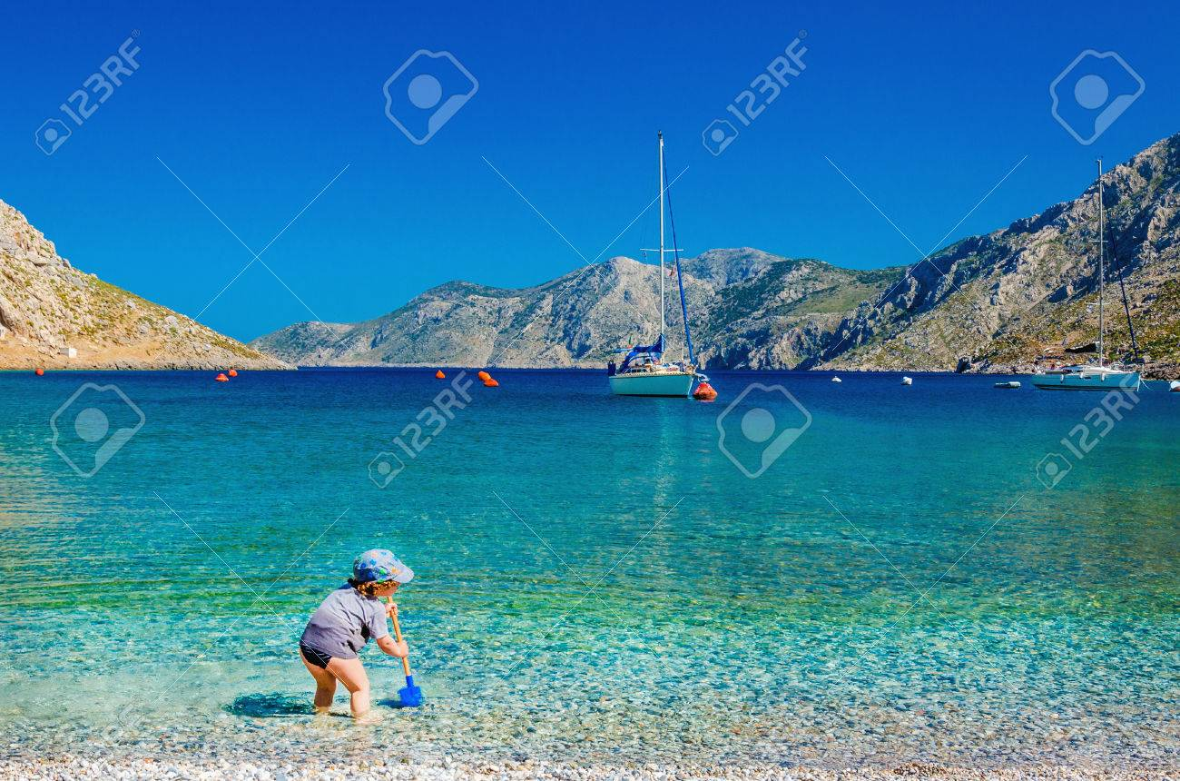 Unidentified child playing at azure sea bay with yacht in background, Greece Stock Photo - 40237410