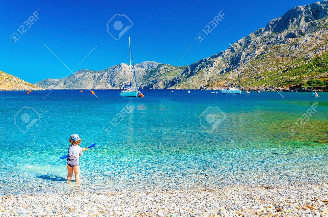 Amazing sea bay on Greek Island with a small boy at play on the seashore, Greece Stock Photo - 40514282