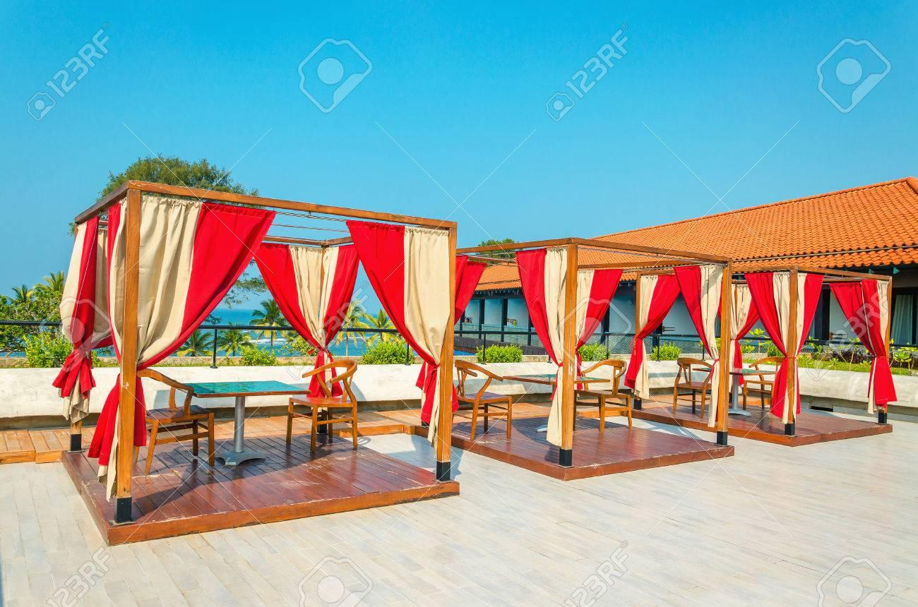 Pergolati con tavoli e sedie, tende rosse in ristorante di hotel ...