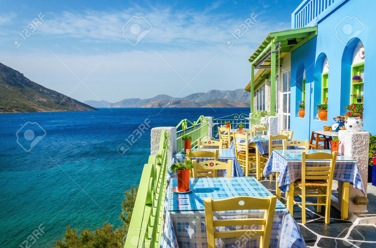 Typical Greek restaurant on the balcony blue building overlooking the sea, Greece Stock Photo - 41589552
