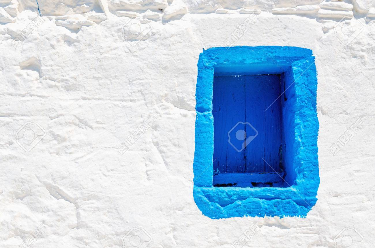 Iconic blue wooden window on white stone wall of typical Greek house, Greece Stock Photo - 44198114