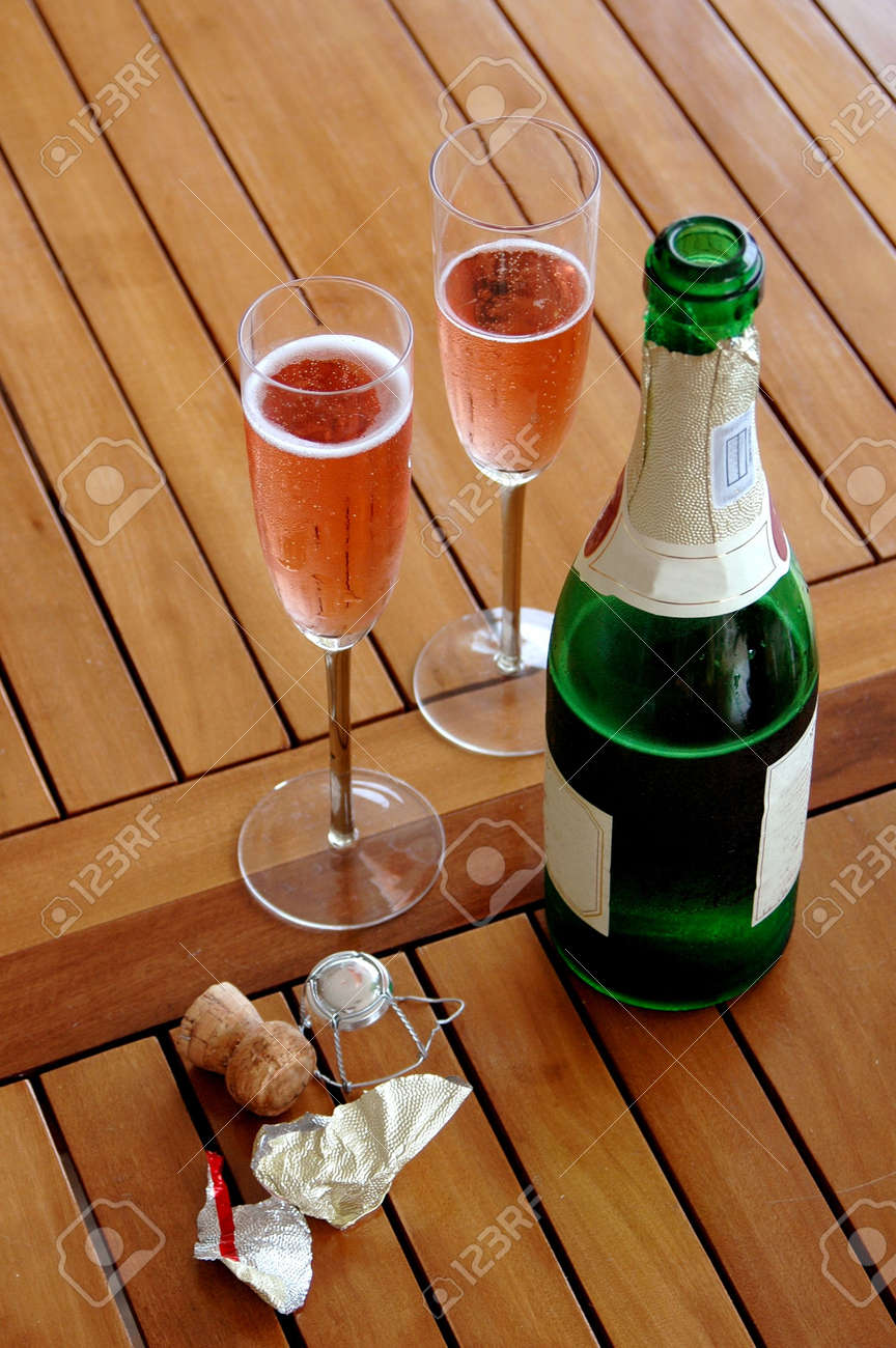 A bottle of red sparkling wine and two champagne glasses on a wooden table outside Stock Photo - 697445