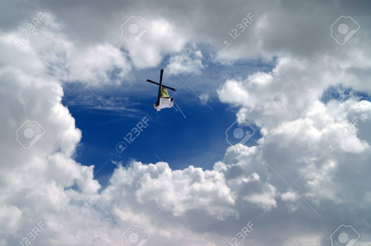 Freestyle ski jumper with crossed skis against blue sky with clouds Stock Photo - 11717578