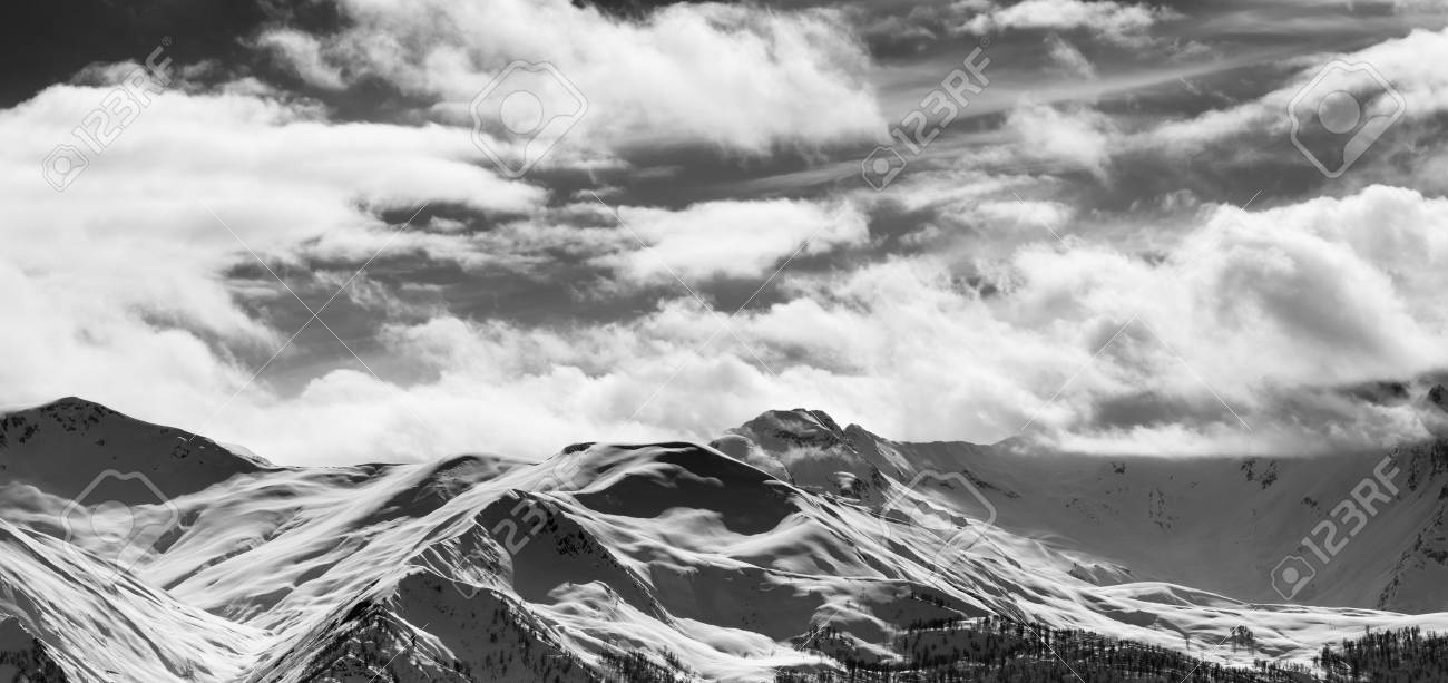 Black and white panoramic view on snow sunlight mountains and