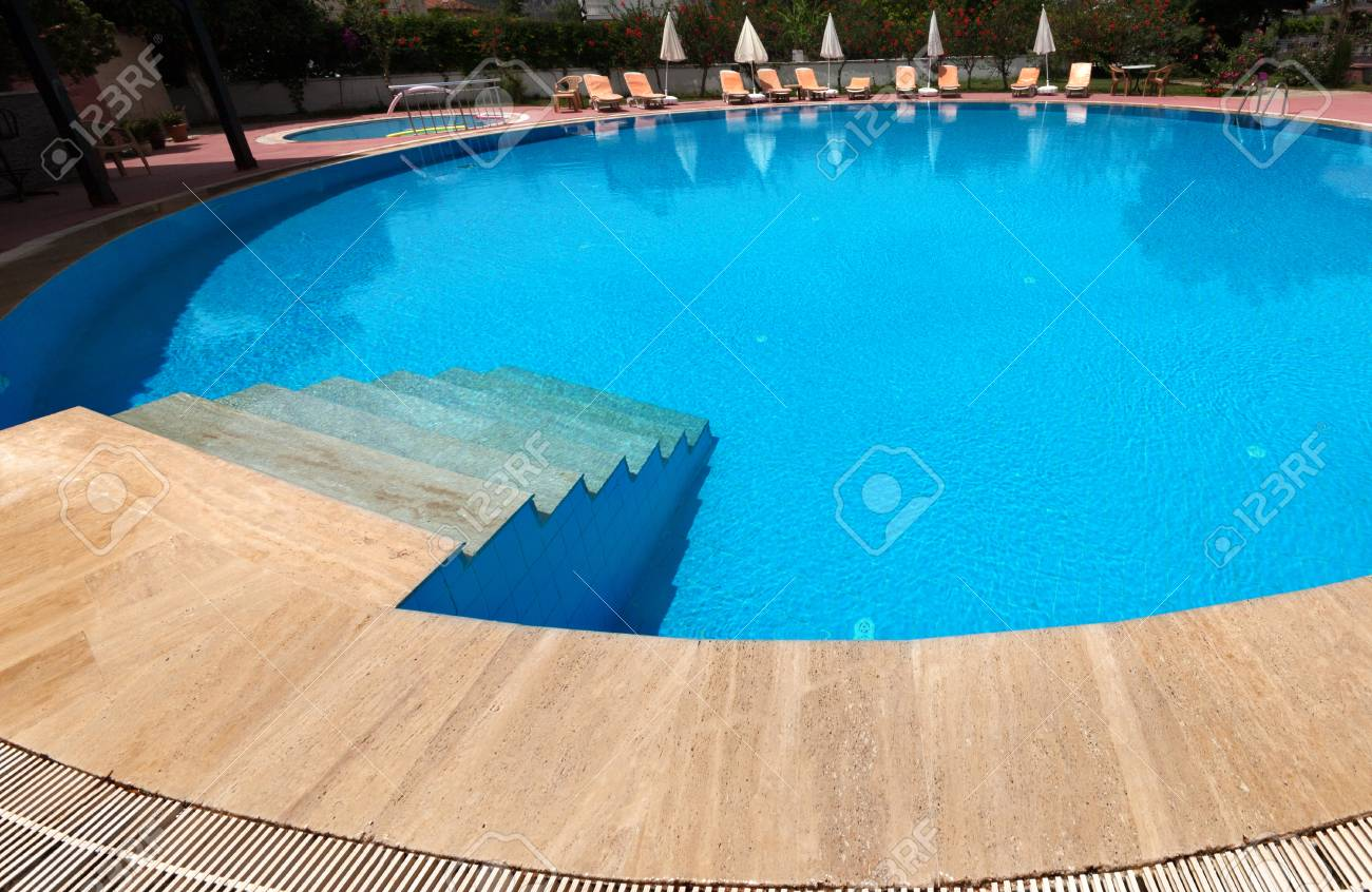 Round swimming pool on open air with beautiful clear water, sun..