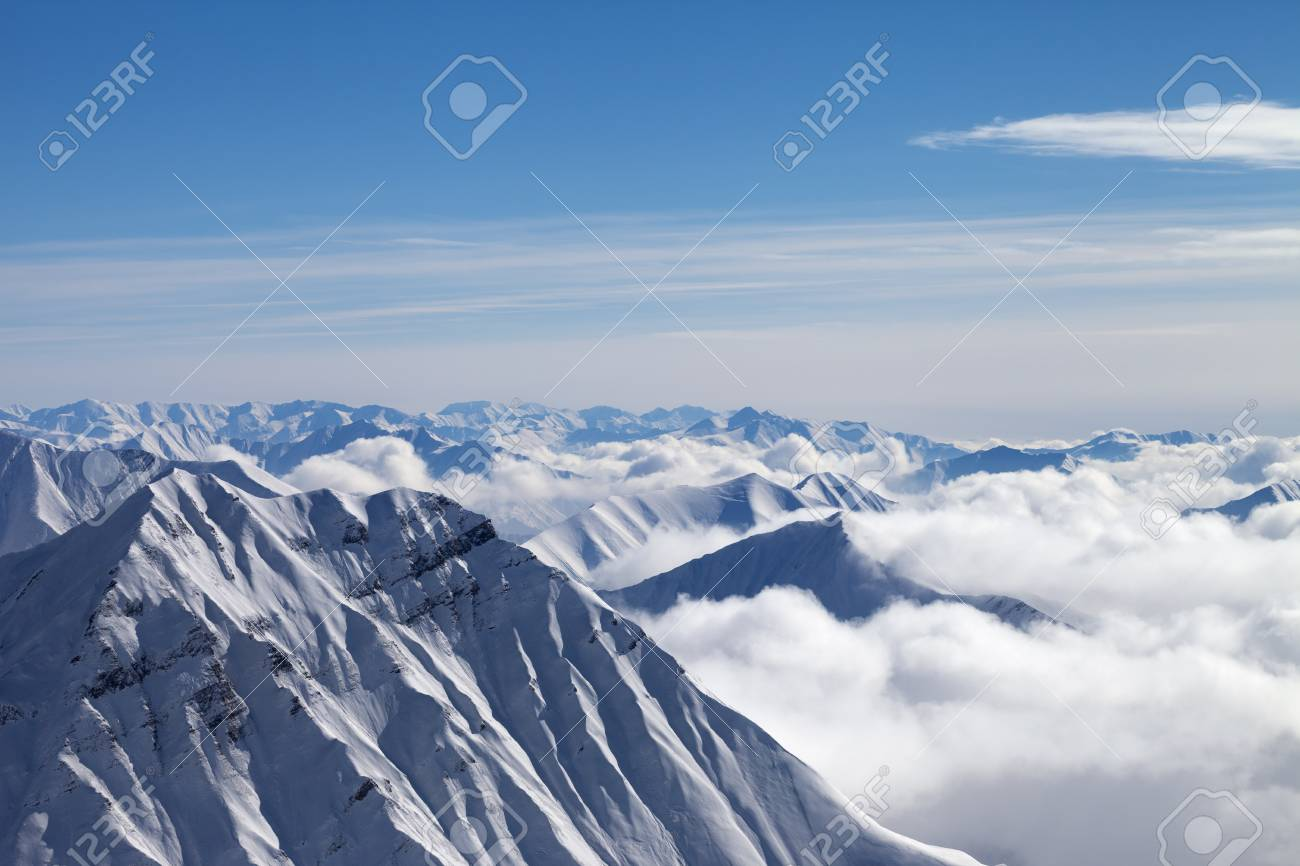 Snowy Mountains In Clouds And Beautiful Blue Sky At Nice Winter