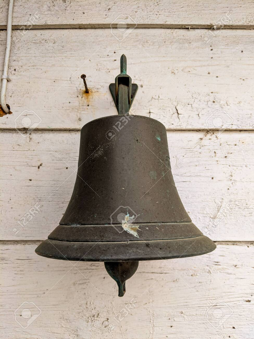 Grey large bell against a wooden old wall at the seaside - 134286096