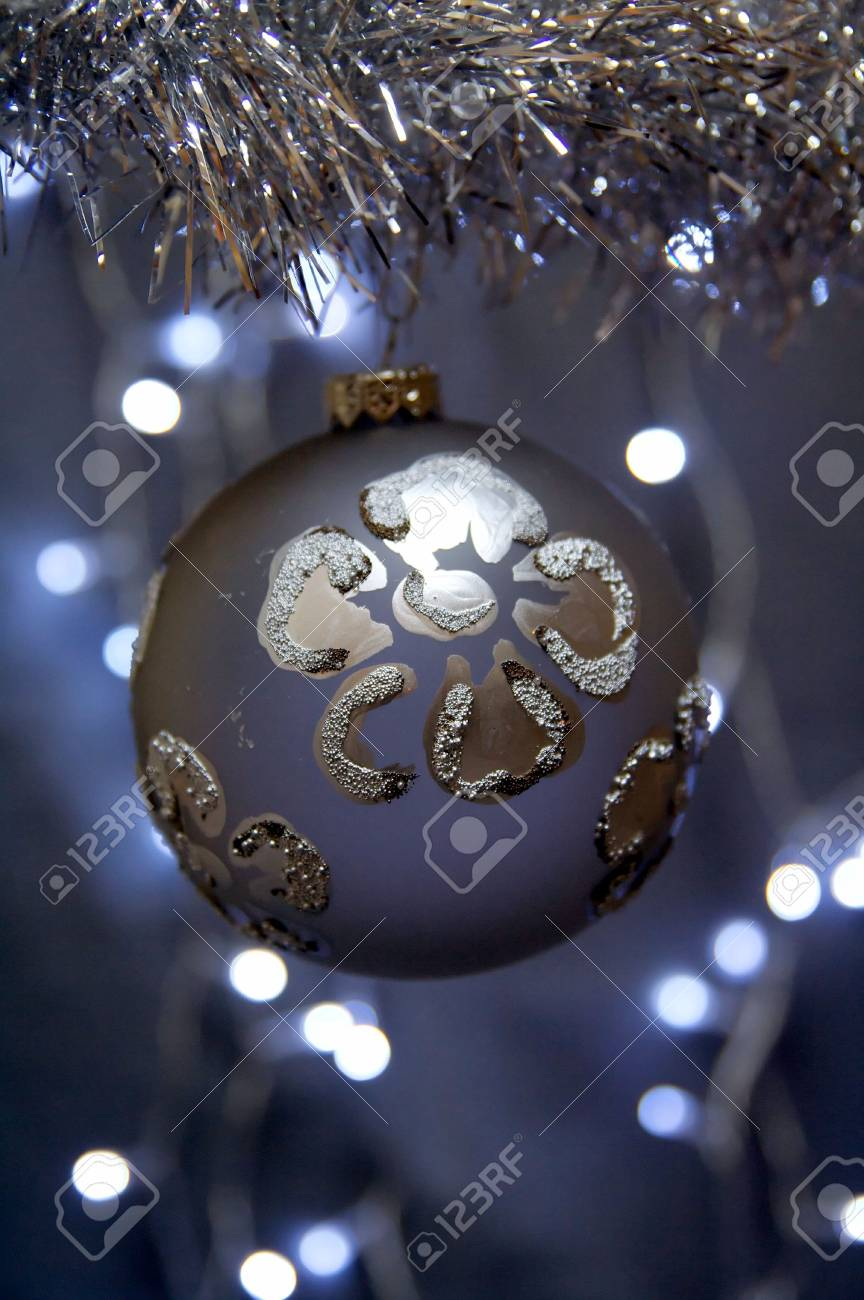 Christmas ornament with silver flower hanging over a background of blurred lights. Stock Photo - 5996524