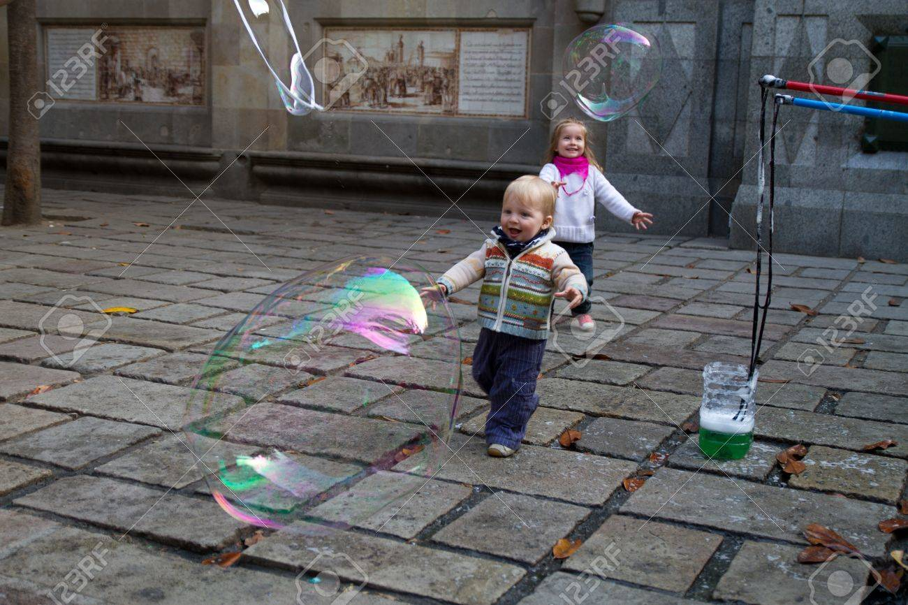 BARCELONA - MAY 14  Unknown street artist making giant soap bubbles and children playing with them on May 14, 2012 in Barcelona, Spain Stock Photo - 13790328
