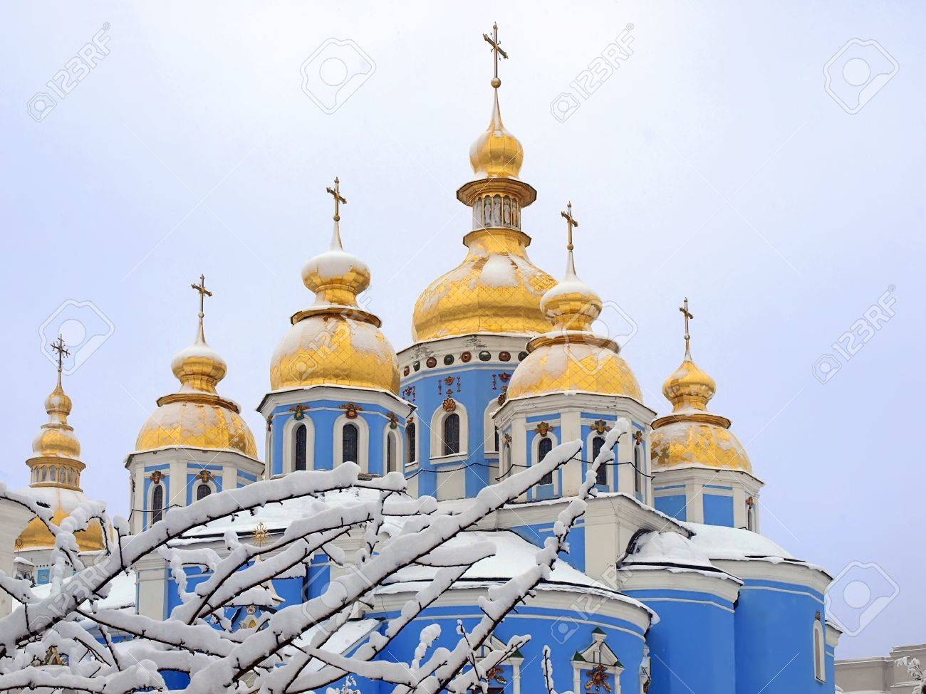 Winter day  St  Michael s Golden Domed Cathedral  On the branches of a tree, on the domes and on the slopes of roofs lies thick layer of snow  Kiev, Ukraine Stock Photo - 16423819