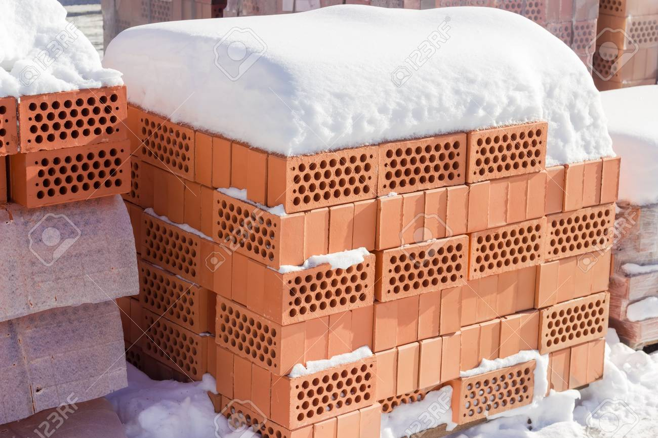 Red Perforated Bricks With Round Holes Covered Snow On A Pallet An Outdoor Warehouse In