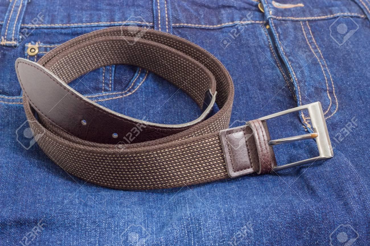 a4e2e1b48a47 Banque d images - Ceinture extensible élastique marron pour hommes avec des  extrémités en cuir et boucle classique se trouve sur un jean bleu