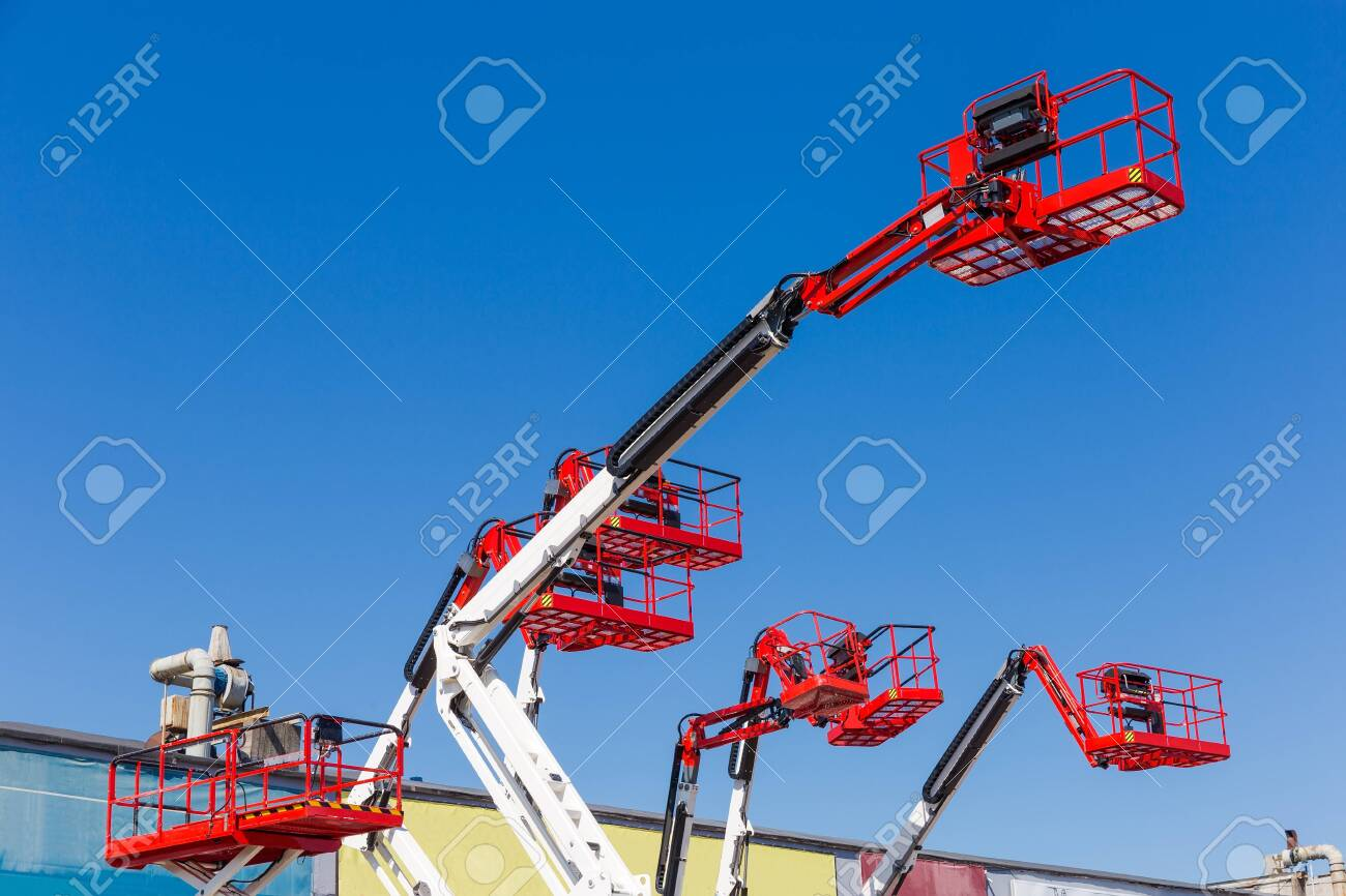 Fragment of the booms with baskets and top parts of different articulated boom lifts and scissor lifts on a background of clear sky - 131420098