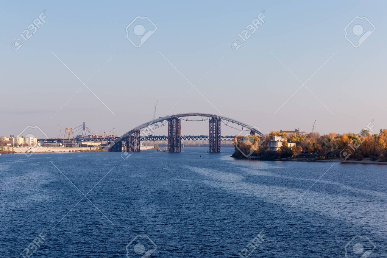 Metro-automobile tied arch bridge with arch-shaped superstructure over river during construction against the other bridges in autumn. Podilsko-Voskresensky Bridge across Dnieper River, Kyiv, Ukraine - 149822486