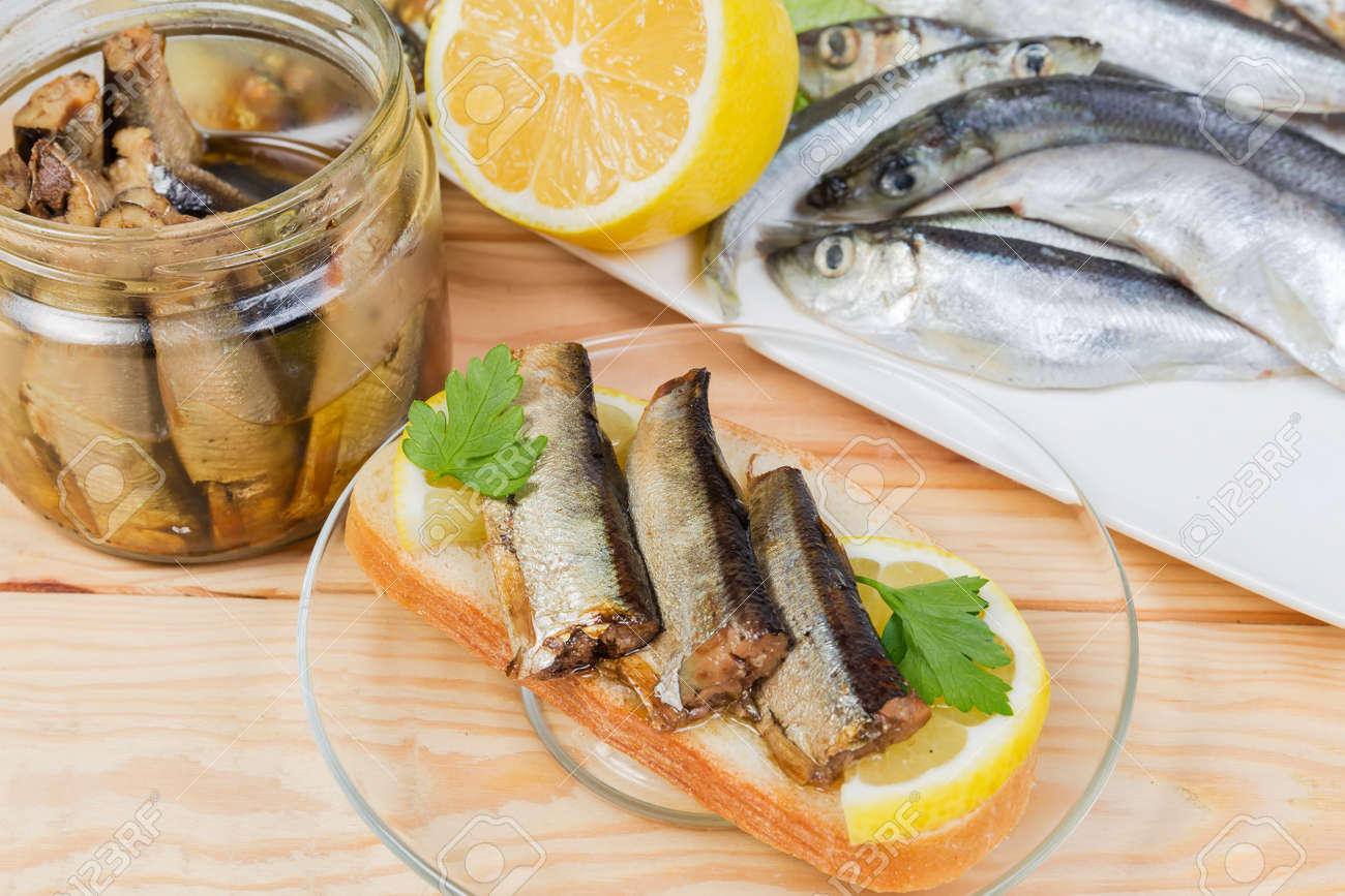 Open sandwich with smoked sprats preserved in vegetable oil and lemon slice against of some ingredients on a rustic table, close-up in selective focus - 168481273