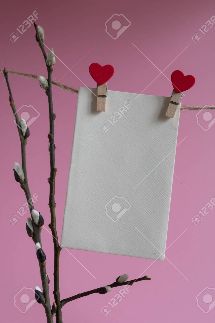 An empty cardboard envelope is hung with wooden clothespins with a red heart and a willow branch on a pink background. Easter holiday concept - 138721954