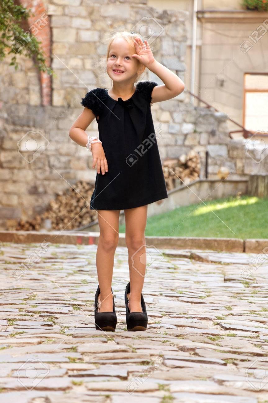 51a33a25d79b4 Foto de archivo - Niña vestida como una mujer adulta. en los zapatos de  tacón alto