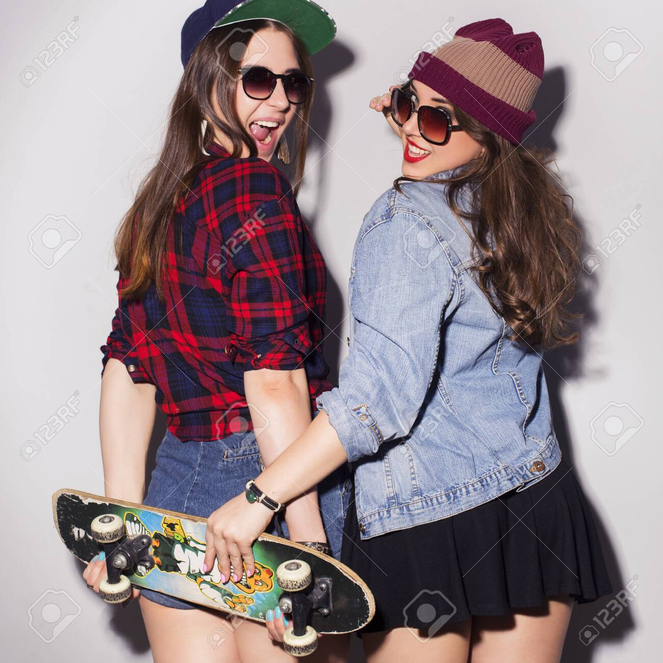 Two beautiful brunette women (girls) teenagers spend time together having fun, make funny faces. Casual hipster outfit, jeans jacket and plaid shirt, with a skateboard - 145673908