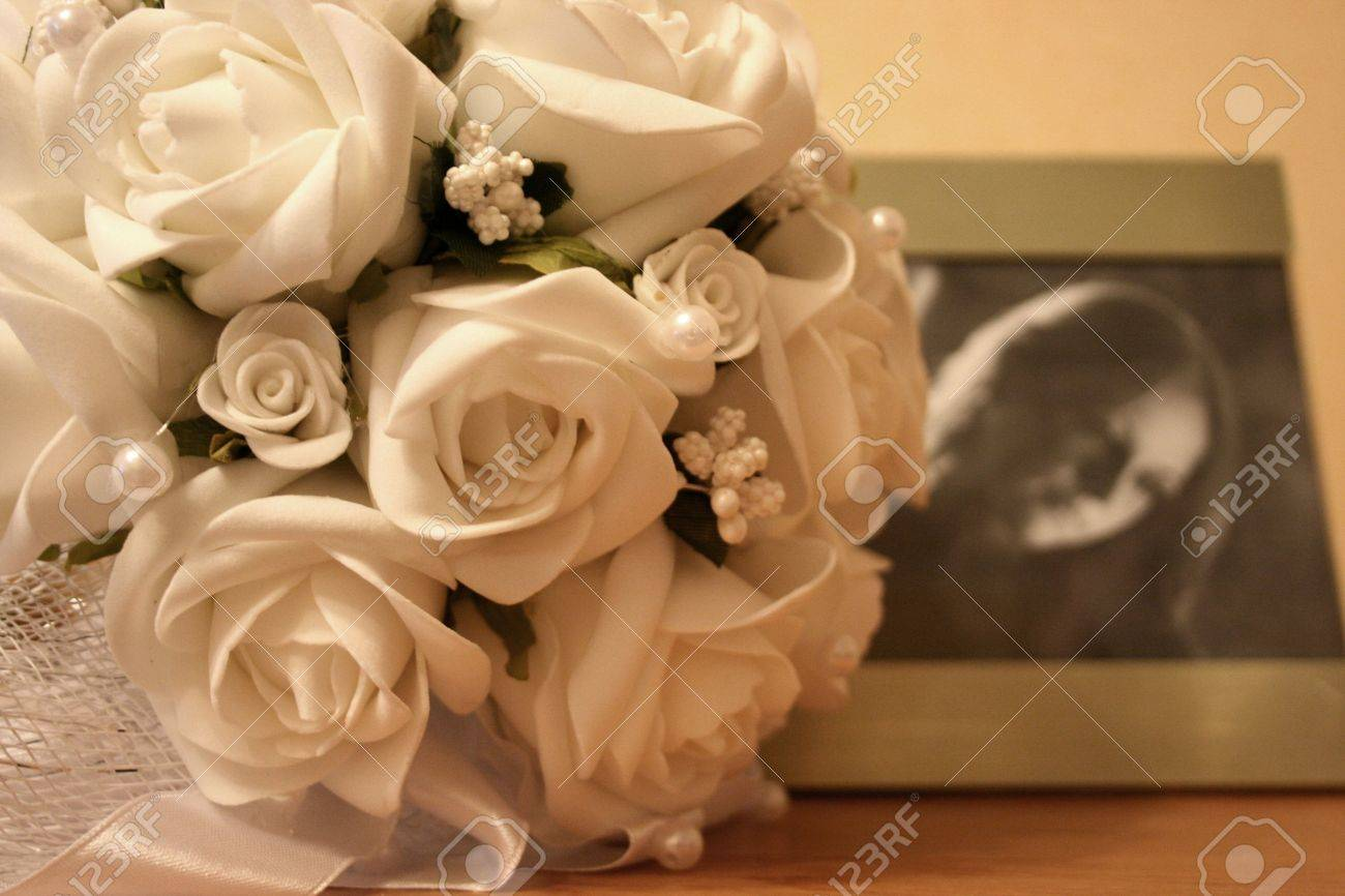 Wedding photo with bunch of flowers and bride�s portrait. Still life Stock Photo - 4383830