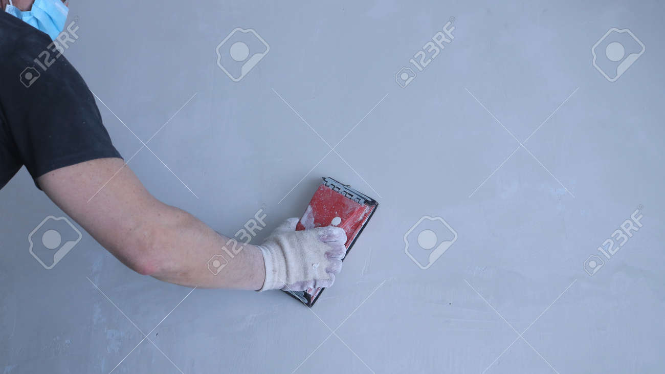 partially visible repairman in the face of a mask with a red wall sander in his right hand against an empty background of a gray wall, sanding gypsum plaster by hand using sandpaper - 162126226