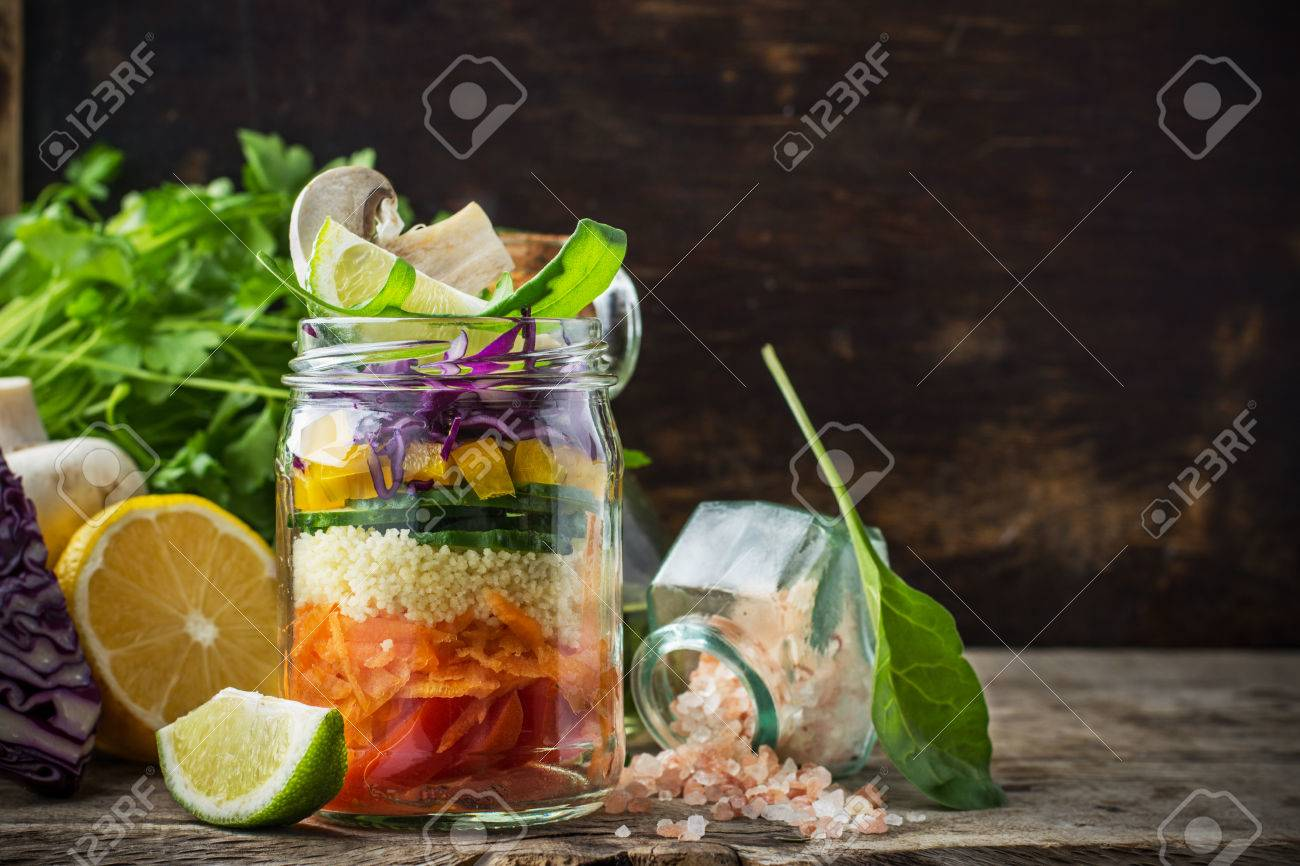 Bright rainbow salad layers of tomatoes, carrots, couscous, yellow pepper, red cabbage, arugula and mushrooms with butter and sea salt on a pink background vegetables and herbs. Trends in healthy eating. Selective focus. - 38445814
