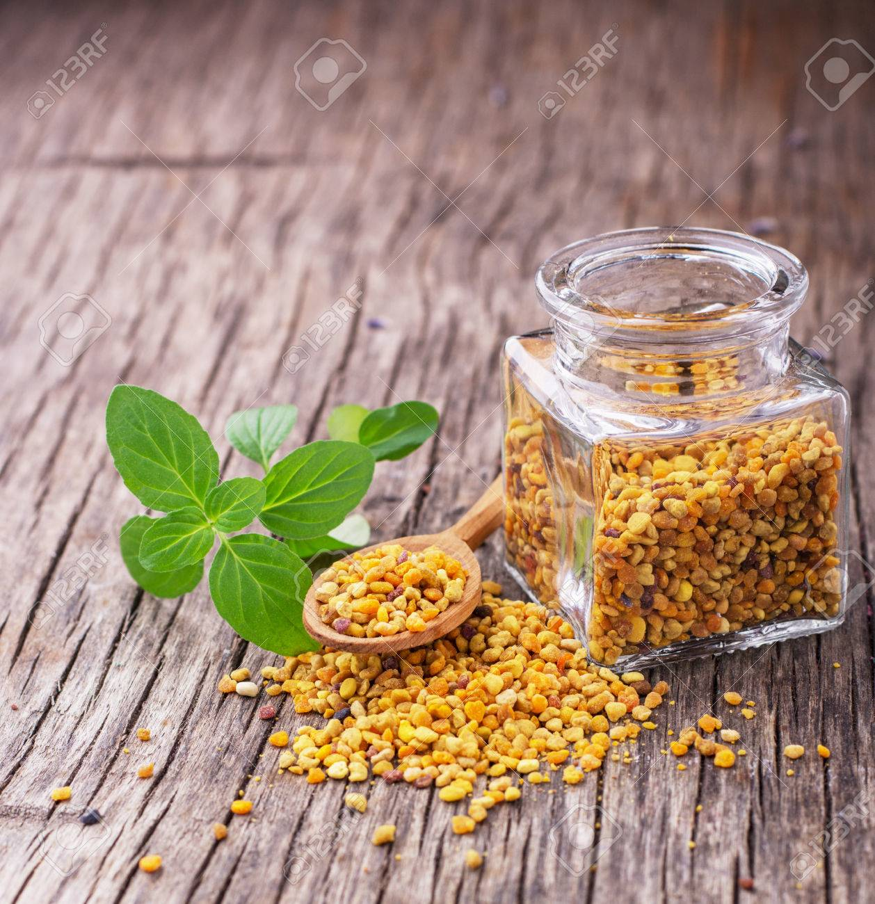Golden Bee Pollen In Small Glass Jars With Honey Comb On The